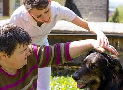 a lady with special needs petting a loving assisted animal therapy canine