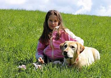 a happy little girl with her autism service dog by her side